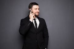 Elegant businessman having a serious conversation on a smart phone against a dark background Stock Image