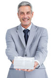 Elegant businessman holding gift Stock Images