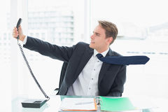 Elegant businessman holding out phone at office Stock Images