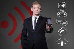 Elegant businessman holding smartphone Stock Images