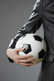 Elegant businessman holding a soccer ball Stock Image