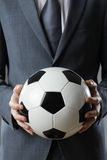 Elegant businessman holding a soccer ball Royalty Free Stock Photos