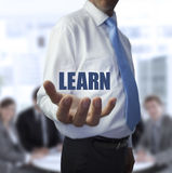 Elegant businessman holding the word learn. In front of a business team Royalty Free Stock Photography