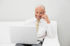 Elegant businessman with laptop sitting on sofa at home Royalty Free Stock Photo
