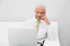 Elegant businessman with laptop sitting on sofa at home Royalty Free Stock Photography