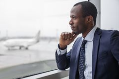 Elegant businessman is looking through glass thoughtfully. Lost in thoughts. Profile of pensive young stylish entrepreneur is standing at airport building. He is Royalty Free Stock Image