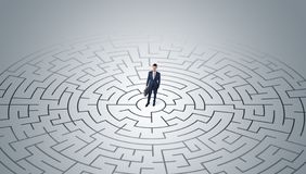 Businessman standing in a middle of a maze stock photography