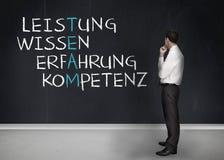 Elegant businessman looking at success terms written in german Stock Photo