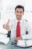 Elegant businessman offering a handshake at desk Royalty Free Stock Photo