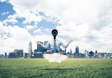 Camera headed man sitting in lotus pose on cloud against modern. Elegant businessman outdoors floating on cloud and camera instead of head Stock Image