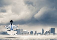 Camera headed man sitting in lotus pose on cloud against modern. Elegant businessman outdoors floating on cloud and camera instead of head Royalty Free Stock Photos