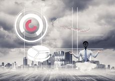 Camera headed man sitting in lotus pose on cloud against modern Stock Images