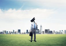 Camera headed man standing on green grass against modern citysca. Elegant businessman outdoors holding jacket on shoulder and camera instead of his head Royalty Free Stock Photo