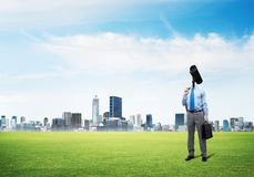 Camera headed man standing on green grass against modern cityscape Royalty Free Stock Photography