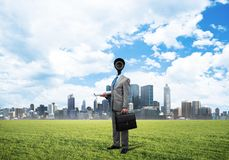 Camera headed man standing on green grass against modern cityscape stock photography