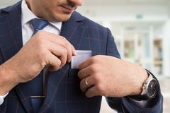 Elegant businessman placing smartphone in pocket. Wearing luxury suit as richness concept Stock Photography