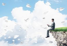 Elegant businessman on rock edge making calls and paper planes f Royalty Free Stock Photography