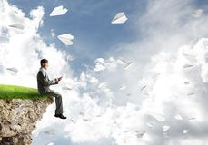 Elegant businessman on rock edge making calls and paper planes flying around Stock Image