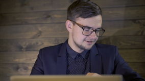 Elegant businessman sitting in cafe and using a laptop stock video