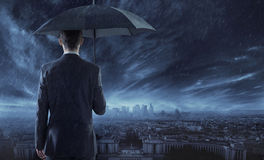 Elegant businessman staring at the city in the night Royalty Free Stock Image