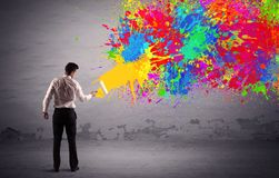 Sales person painting colorful splatter. An elegant businessman in suit painting colorful splatter, bright colors on grey urban wall with a paint roller in his Stock Photos