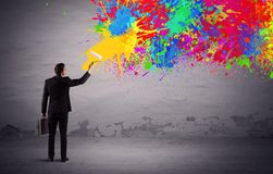 Sales person painting colorful splatter. An elegant businessman in suit painting colorful splatter, bright colors on grey urban wall with a paint roller in his Stock Images