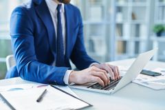Typing on keypad. Elegant businessman in suit typing on keypad while sitting by desk in front of laptop in office stock photos