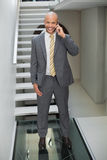 Elegant businessman using cellphone against staircase in office Stock Photo
