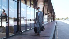 Elegant businessman wearing protective mask in airport. Young mail entrepreneur in formalwear. Pandemic, new rules of