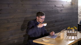 Elegant businessman working with a laptop and drinking coffee in cafe stock footage