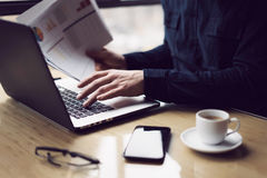 Elegant businessman working at sunny office on laptop while sitting at the wooden table.Man holding paper reports in. Hands.Blurred background royalty free stock photography