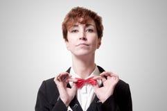 Elegant businesswoman adjusting bow tie. On gray background Royalty Free Stock Photos