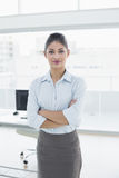 Elegant businesswoman with arms crossed in office Stock Photos