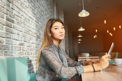 Elegant businesswoman chatting on touch pad while sitting in comfortable coffee shop. Young female entrepreneur reading electronic book on digital tablet during Stock Image