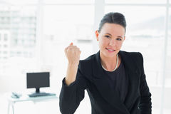 Elegant businesswoman clenching fist in office Royalty Free Stock Images