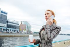 Calling during business trip. Elegant businesswoman with drink speaking by smartphone during trip by steamship Stock Photo