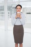 Elegant businesswoman enjoying coffee smell with eyes closed in office Royalty Free Stock Photos