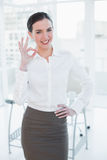Elegant businesswoman gesturing ok sign in office Royalty Free Stock Photography