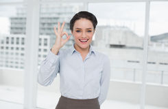 Elegant businesswoman gesturing ok sign in office Stock Photo