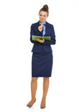 Elegant businesswoman holding notebook with pen on chin Royalty Free Stock Photos