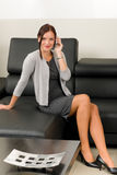 Elegant businesswoman on leather sofa call phone Royalty Free Stock Photos