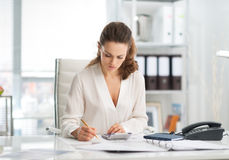 Elegant businesswoman making calculations at desk Royalty Free Stock Photography