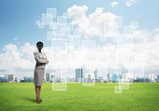 Camera headed woman standing on green grass against modern cityscape Stock Photo