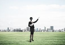Camera headed woman standing on green grass against modern citys Stock Images