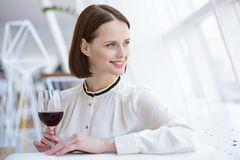 Elegant businesswoman relaxing in cafe. Happy young woman is drinking red wine in restaurant. She is sitting at table and looking through window dreamingly. Lady Stock Image