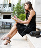 Businesswoman with folder. Elegant businesswoman sitting on a classic buildings steps, taking notes in her agenda Stock Images