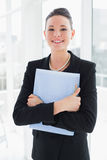 Elegant businesswoman standing against office glass wall with folder Stock Photo