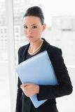 Elegant businesswoman standing against office glass wall with folder Royalty Free Stock Photos