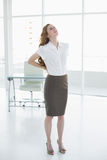 Elegant businesswoman suffering from back ache in office Royalty Free Stock Photo