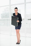 Elegant businesswoman in suit carrying briefcase in office Royalty Free Stock Images